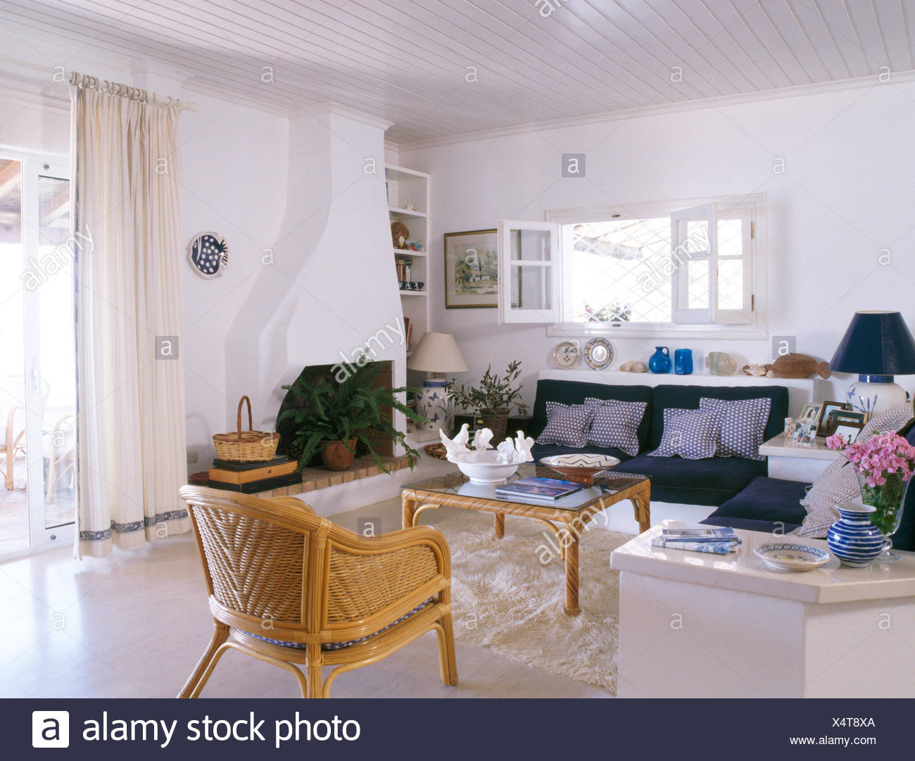 Cane Chair And Fitted Sofa With Blue Cushions In White Coastal Sitting Room With White Curtains On French Windows Stock Photo Alamy