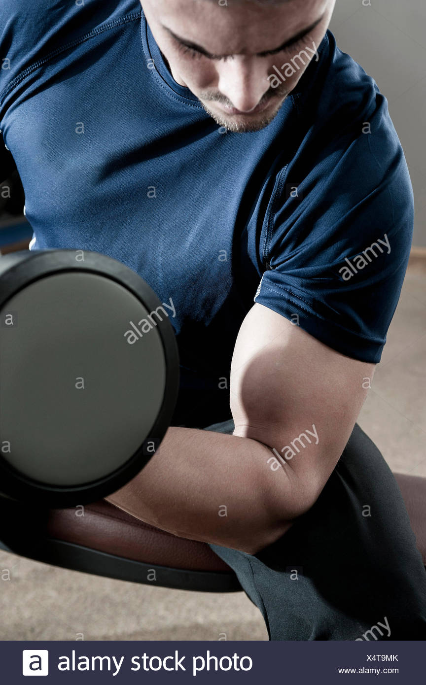 Young man in gym lifting dumbbell - Stock Image