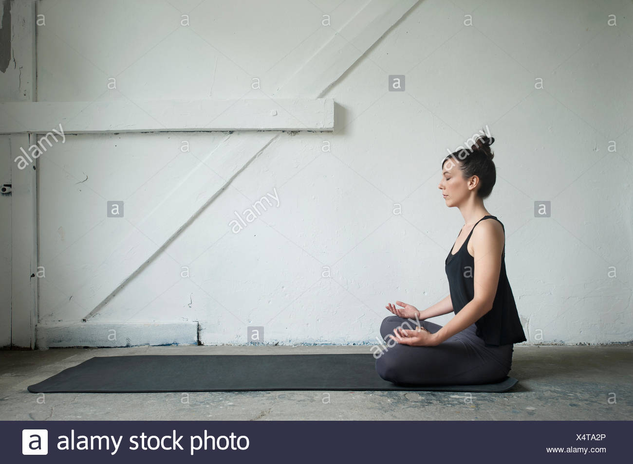 Side profile of a mid adult woman practicing lotus pose in yoga studio, Munich, Bavaria, Germany - Stock Image