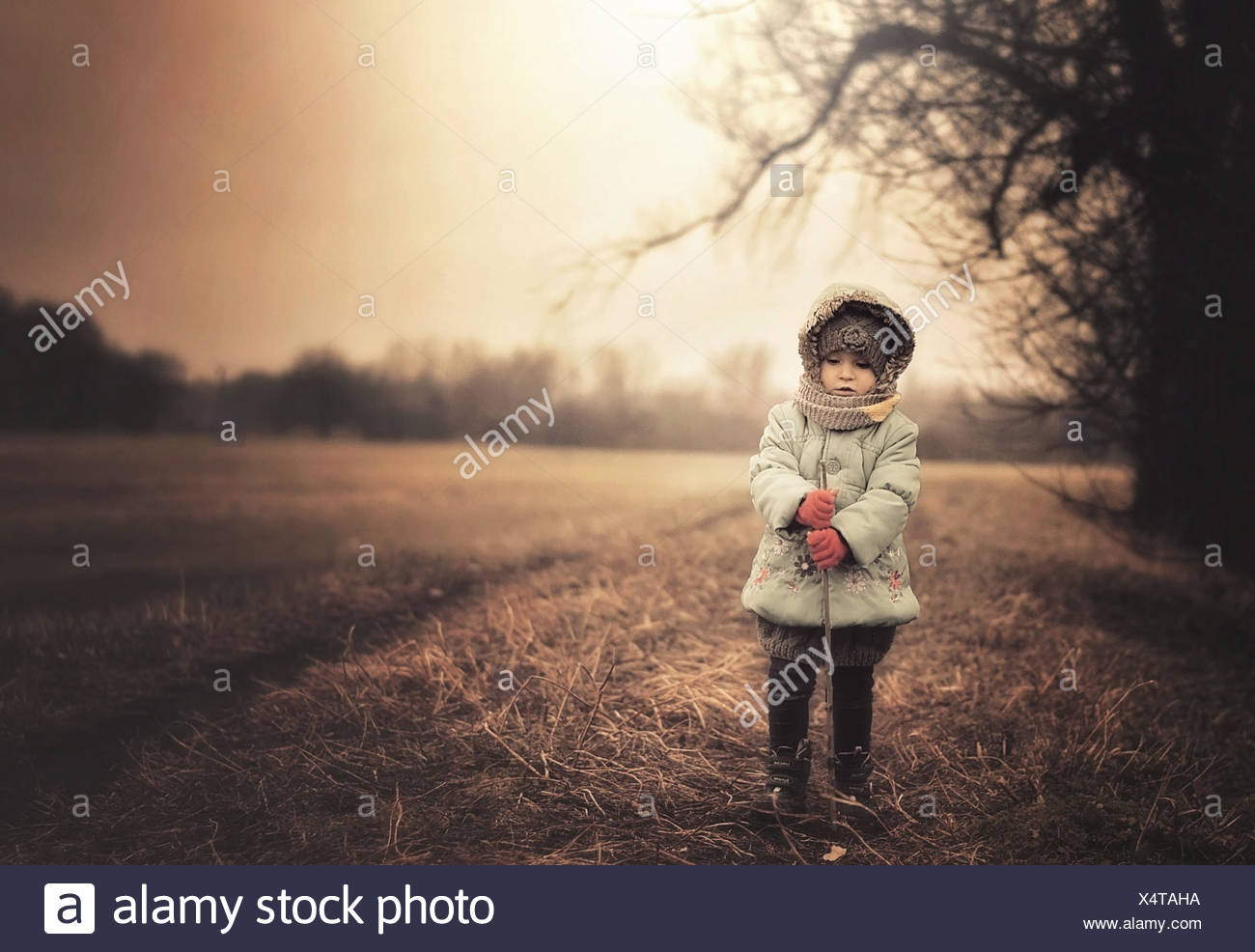 Poland, Girl wearing warm clothes standing on field - Stock Image