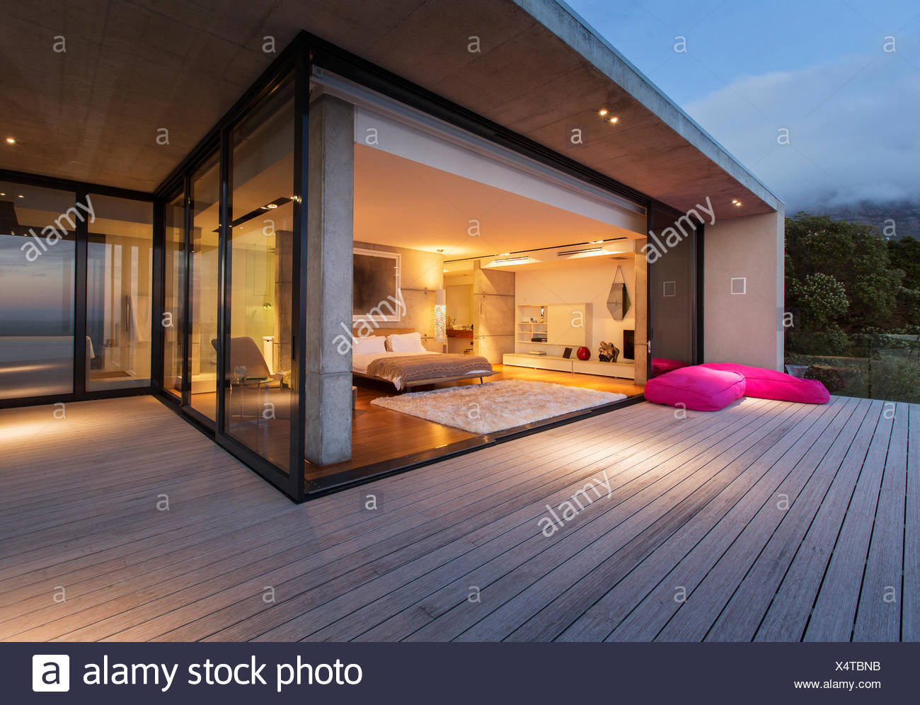 Sliding glass doors onto bedroom of modern house - Stock Image