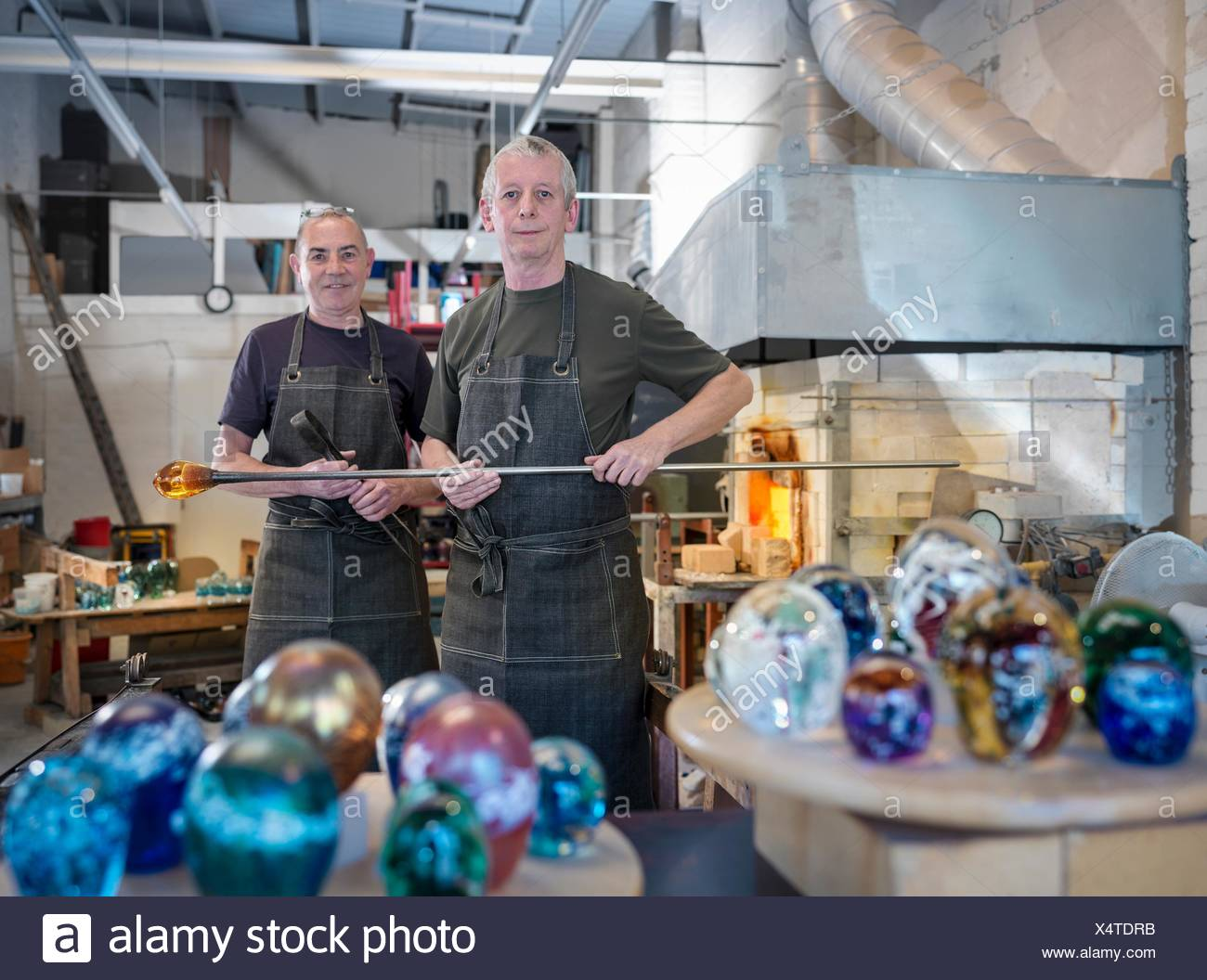 Artisan glassblowers in workshop with furnace and finished glassware - Stock Image