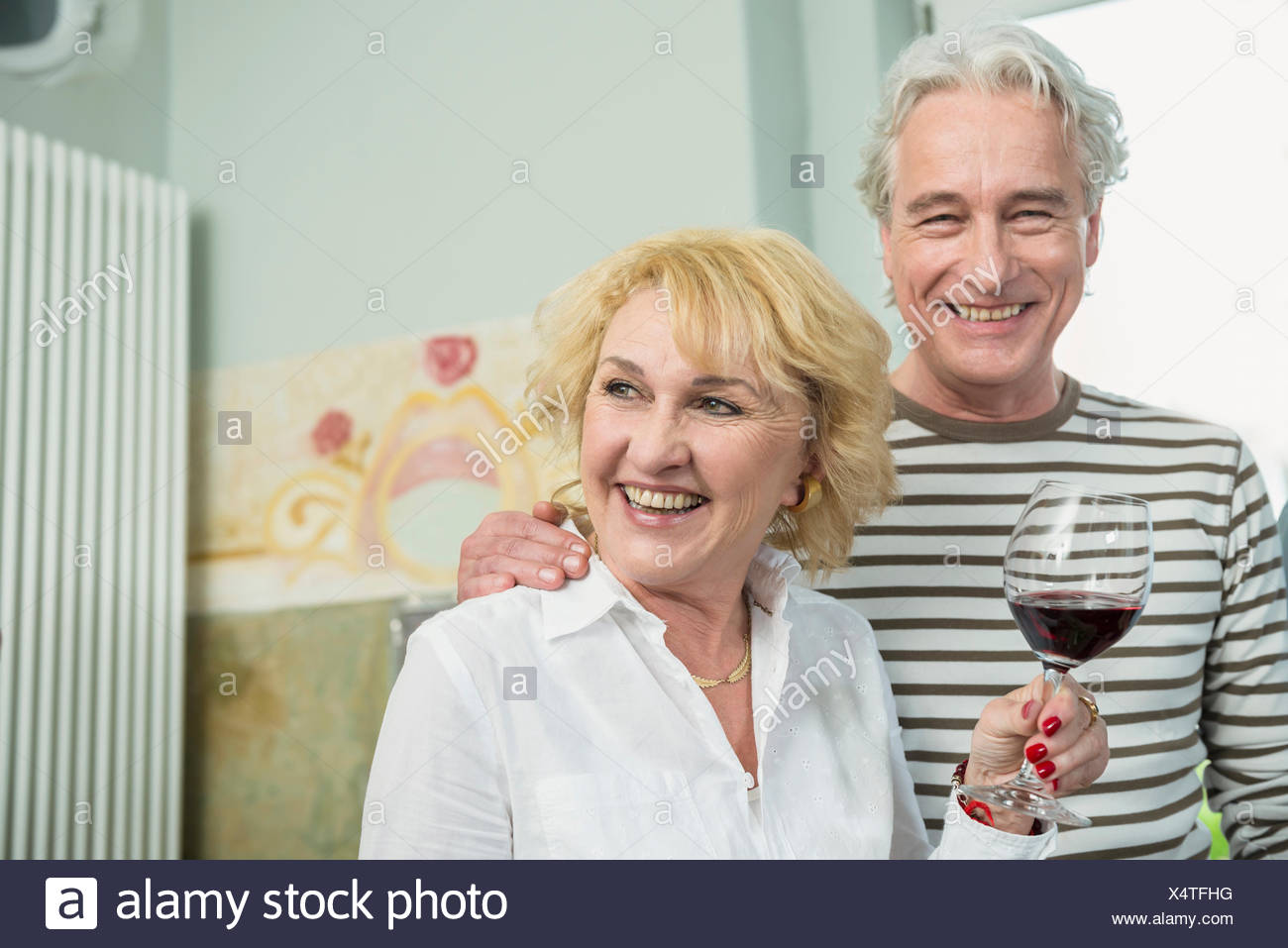 Mature couple drinking wine, smiling Stock Photo