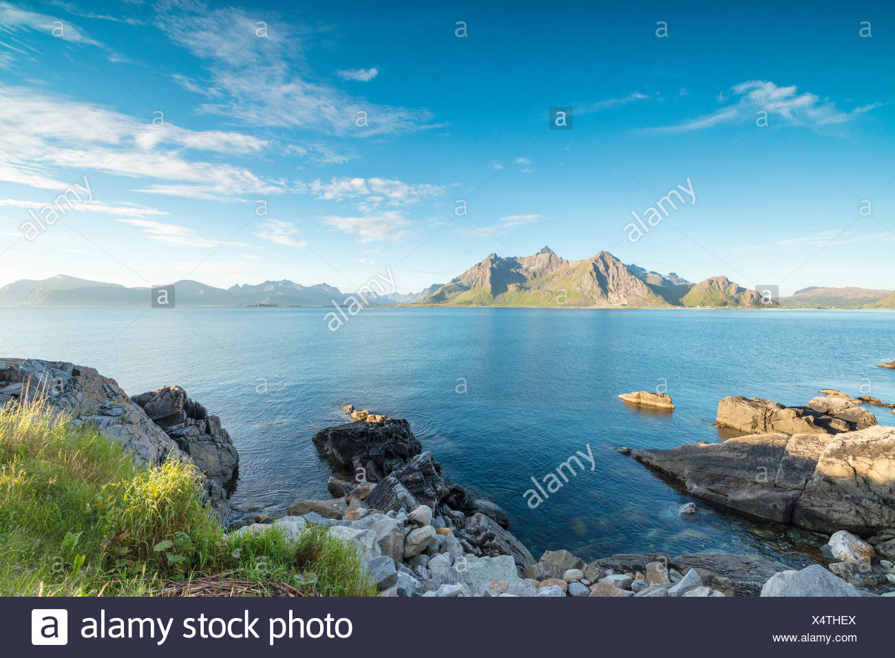 Sun shines on the blue sea and the rocky peaks at night during summer Vikten Nord Trøndelag Lofoten Islands Norway Europe - Stock Image