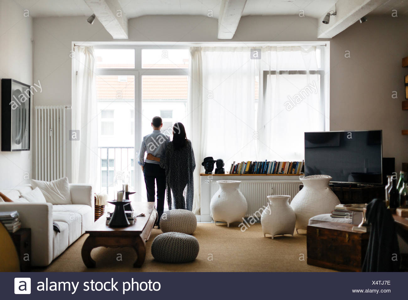 Germany, Couple looking through window in living room Stock Photo