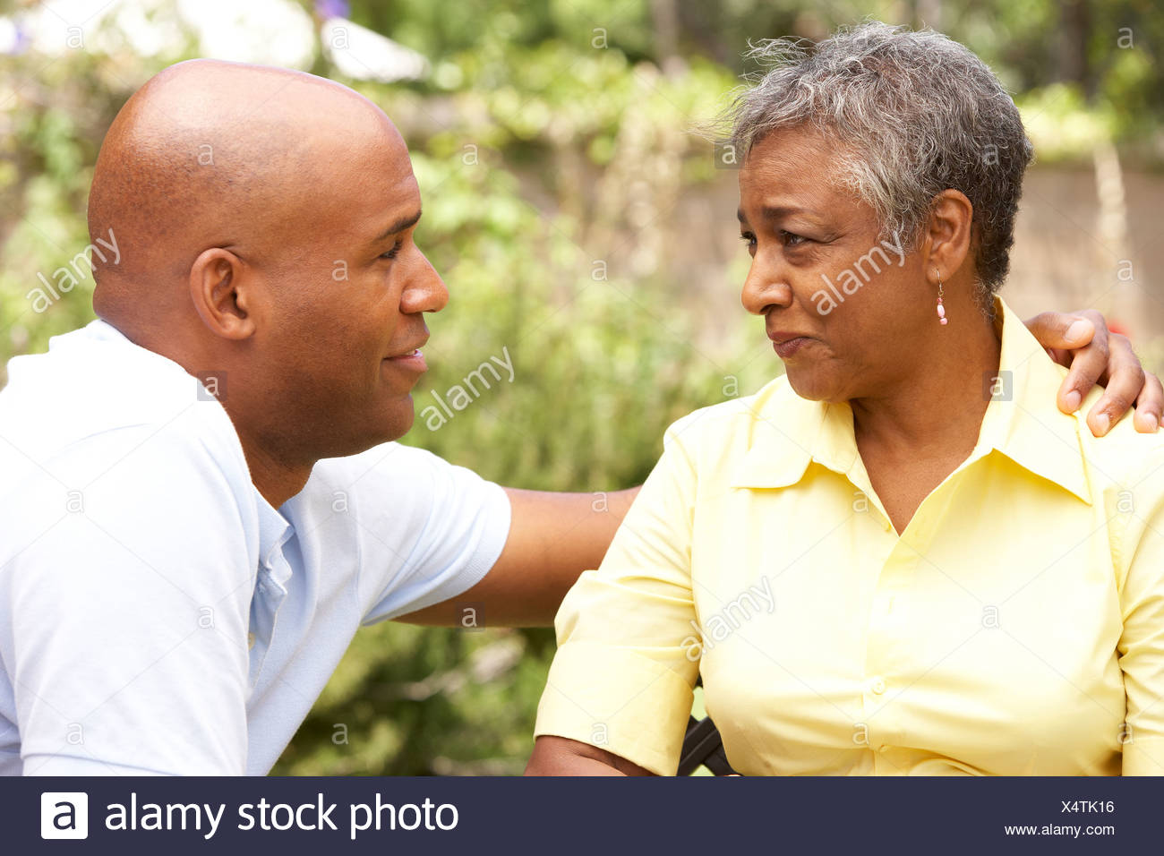 Senior Woman Being Consoled By Adult Son - Stock Image