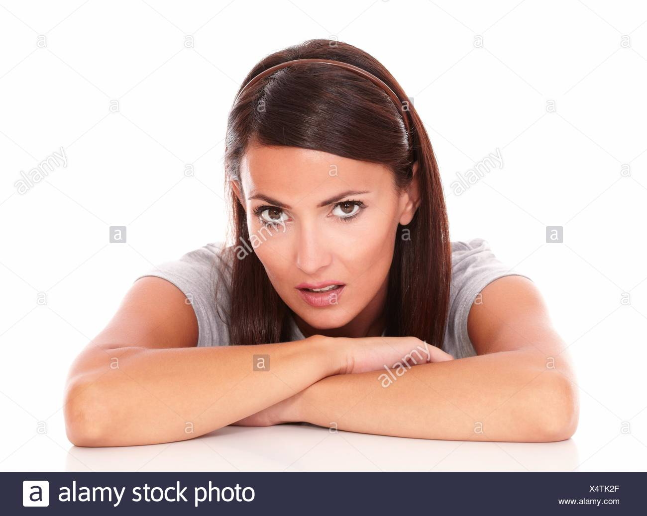 Head and shoulders portrait of unsmiling beautiful female looking at camera on isolated background. - Stock Image