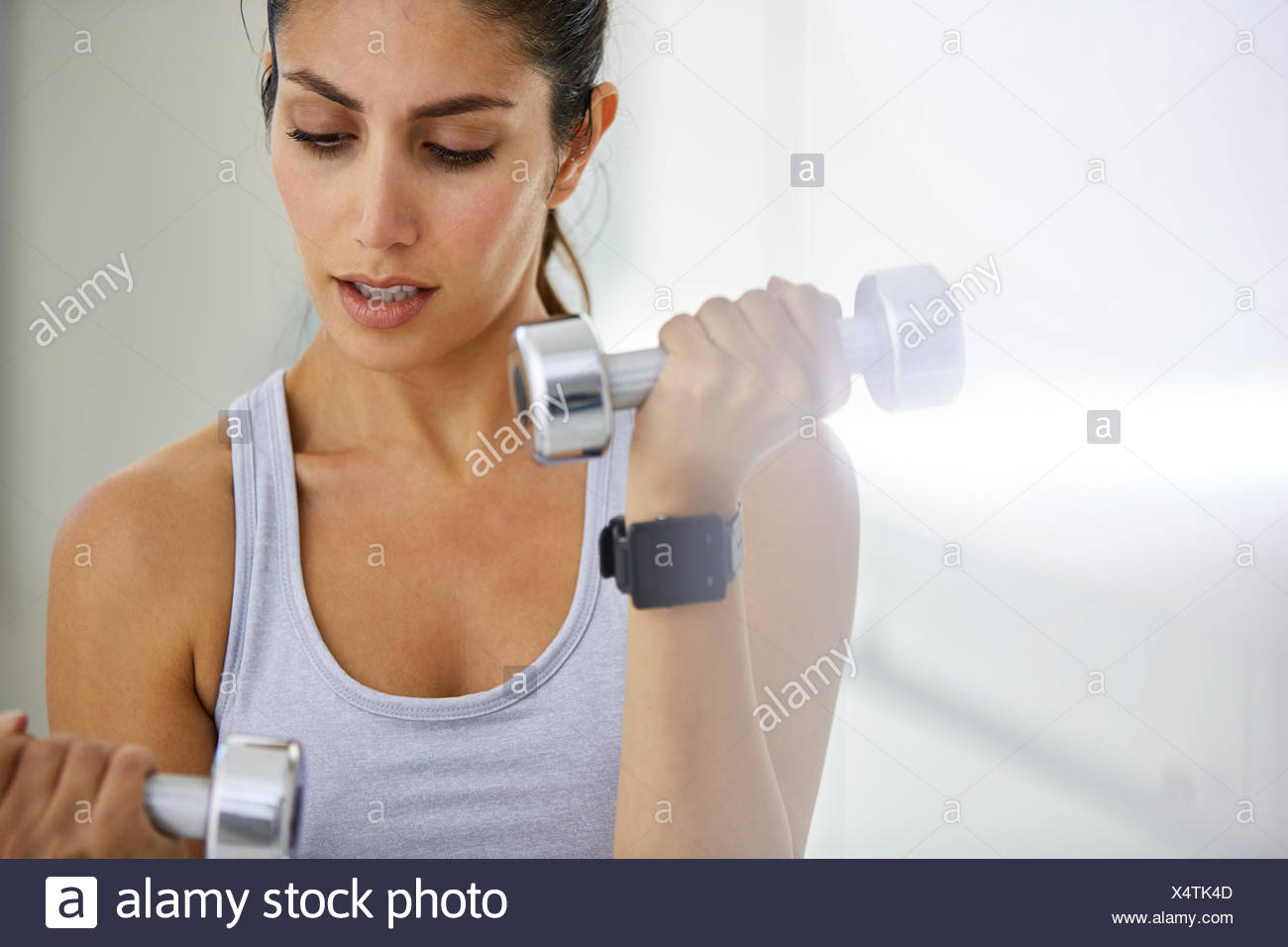 Focused woman doing biceps curls with dumbbells - Stock Image