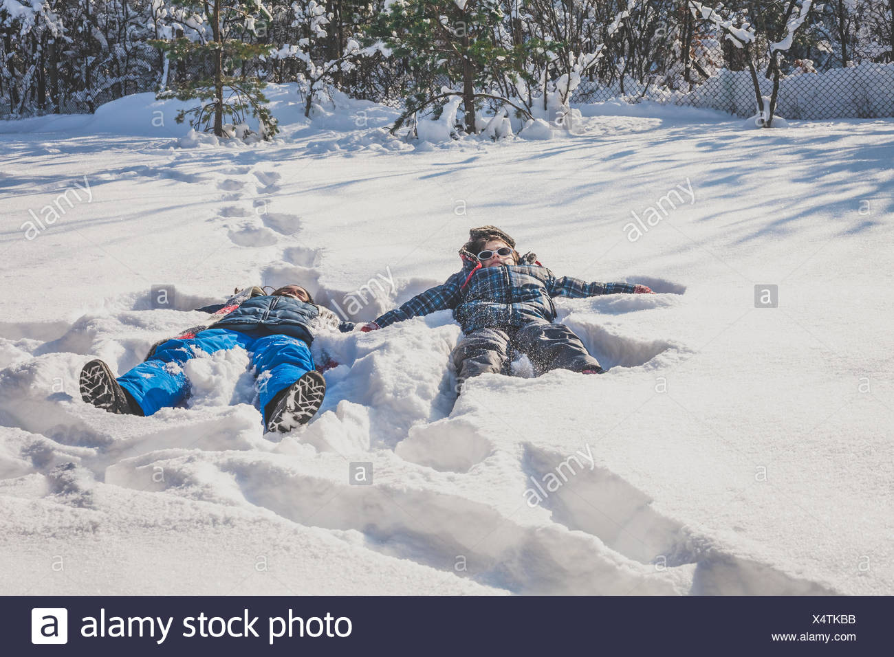 Boy and girl lying in snow making snow angels in the snow - Stock Image