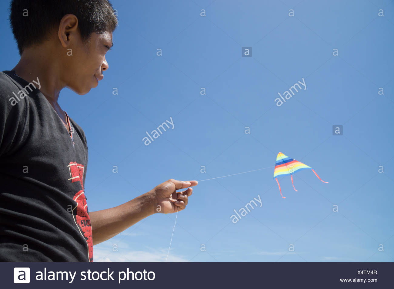 Portrait of boy flying kite - Stock Image