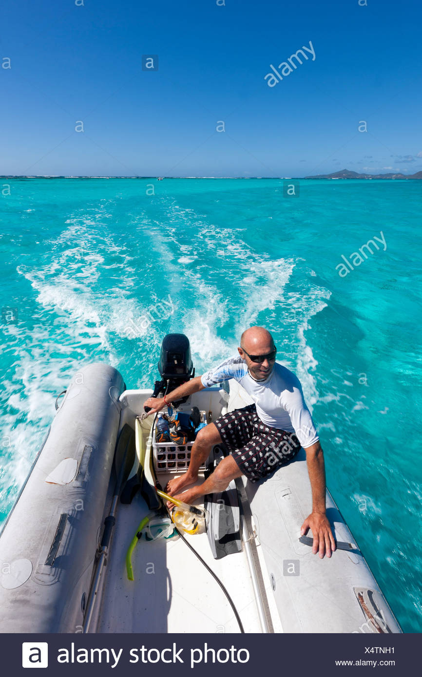 Man in dinghy on Caribbean Sea - Stock Image