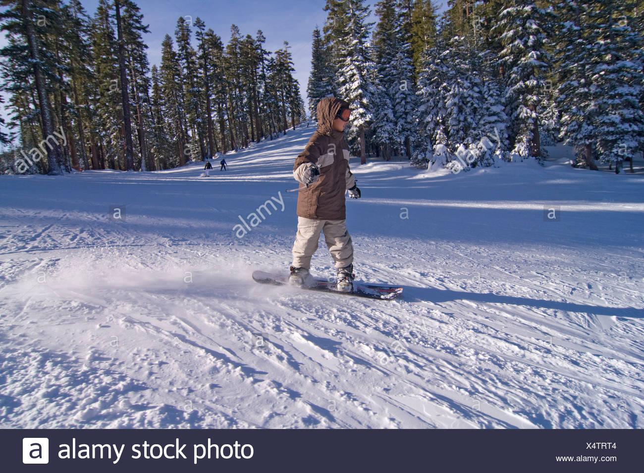 A boy snowboarding at Sierra at Tahoe ski resort near Lake Tahoe in California Stock Photo
