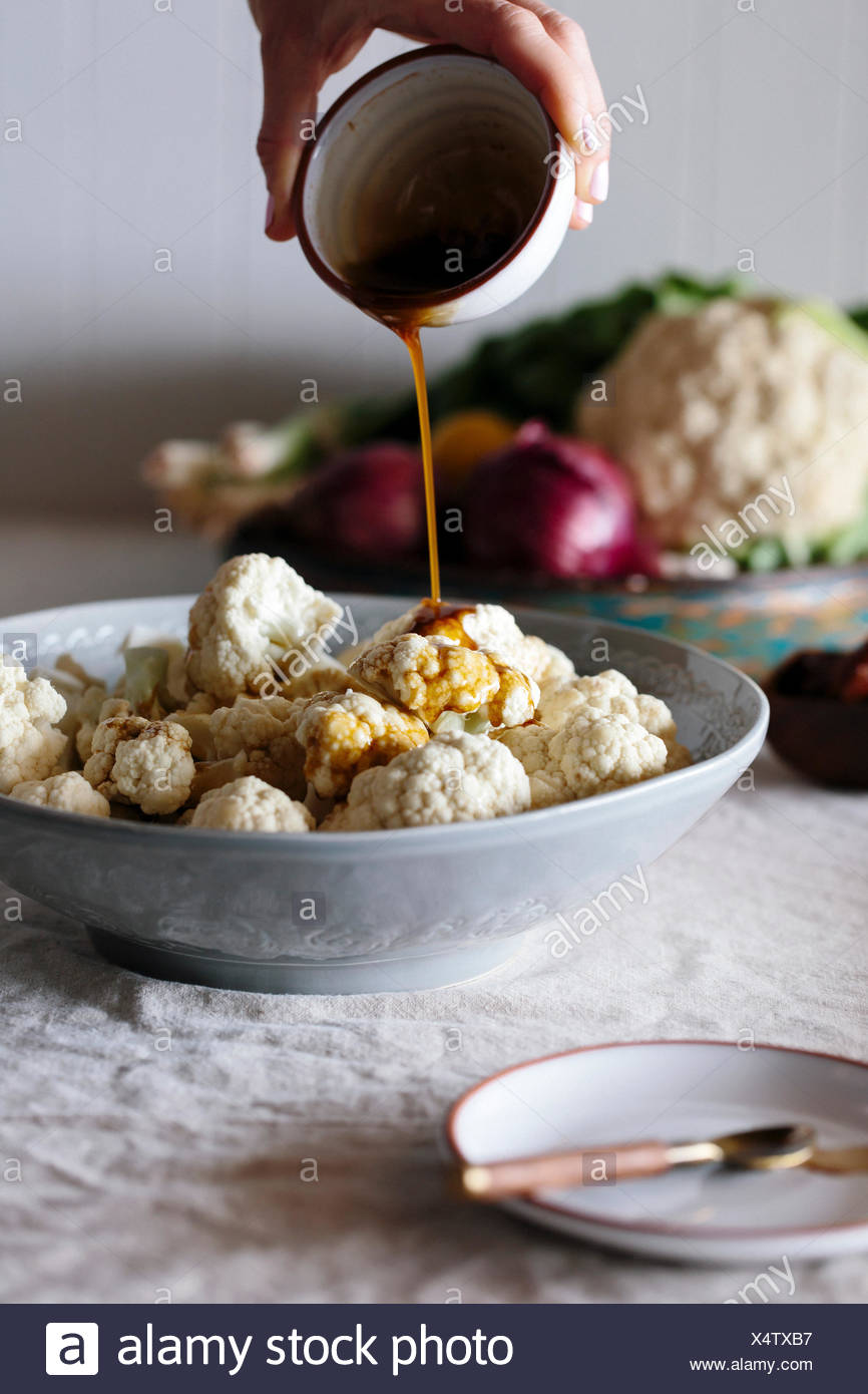 Raw cauliflower florets are being drizzled with a spicy dressing by a person. - Stock Image
