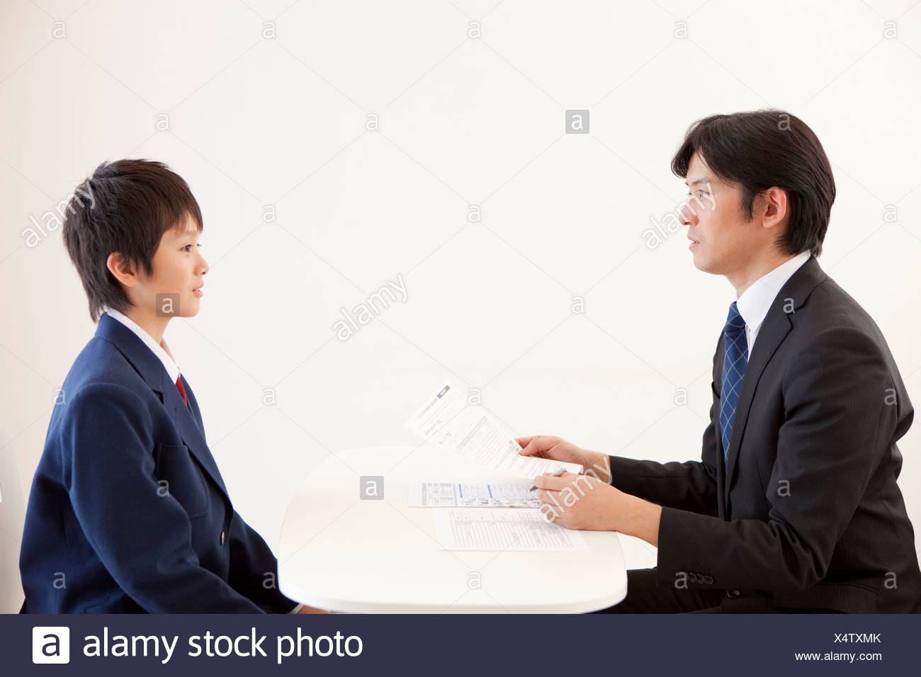 Junior High School Boy and Teacher Having a Meeting - Stock Image