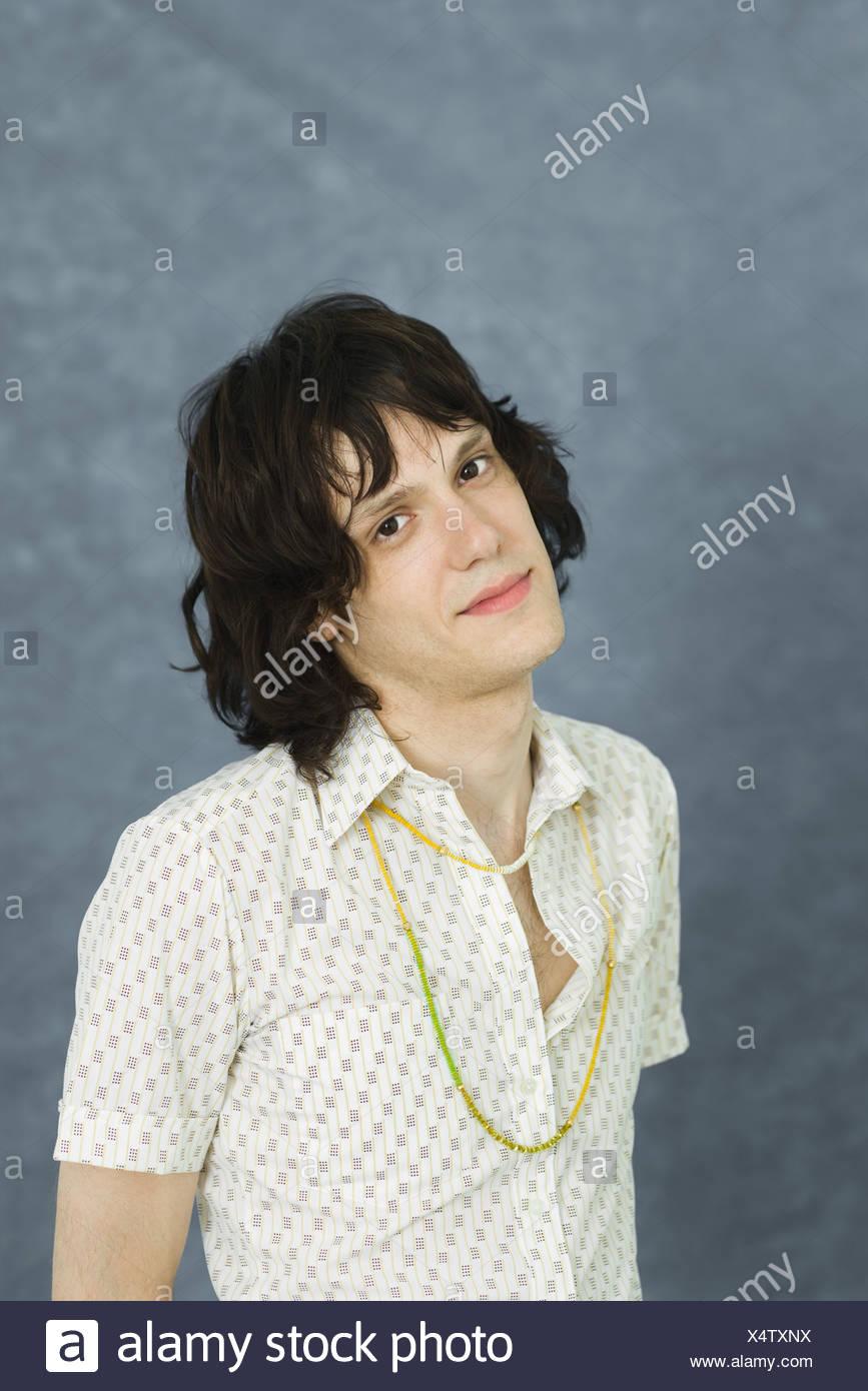 Teenage boy looking at camera, head tilted, portrait - Stock Image
