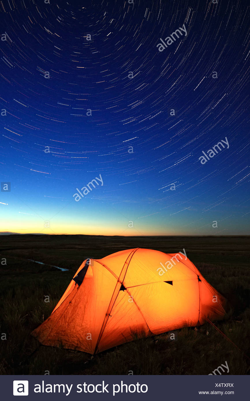Tent lit up night overlooking Frenchman River - Stock Image