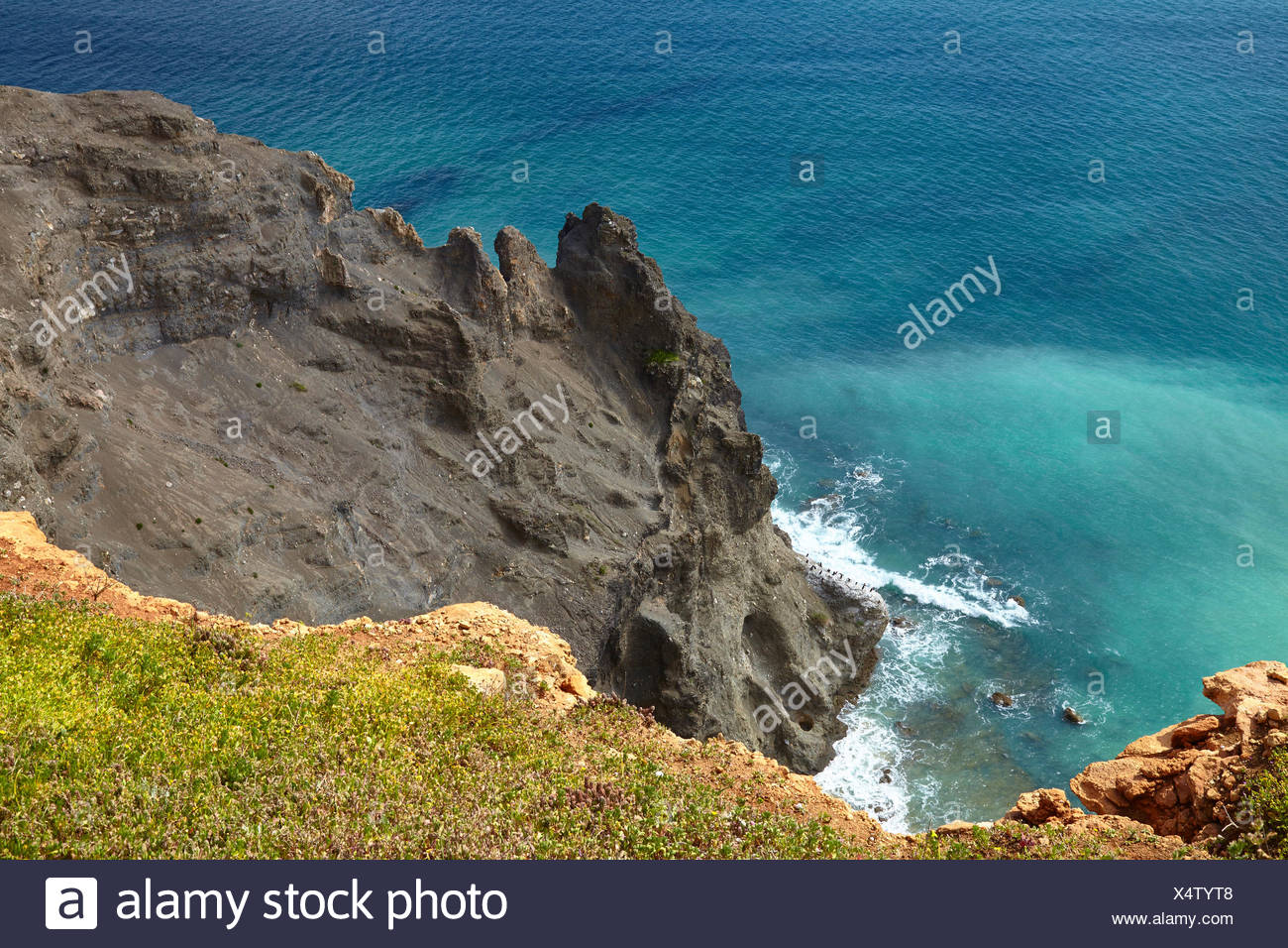 black basalt rock as a geologic anomaly at the rock coast at the Atlantic with Luz, west of Lagos, Algarve, Portugal, Europe - Stock Image