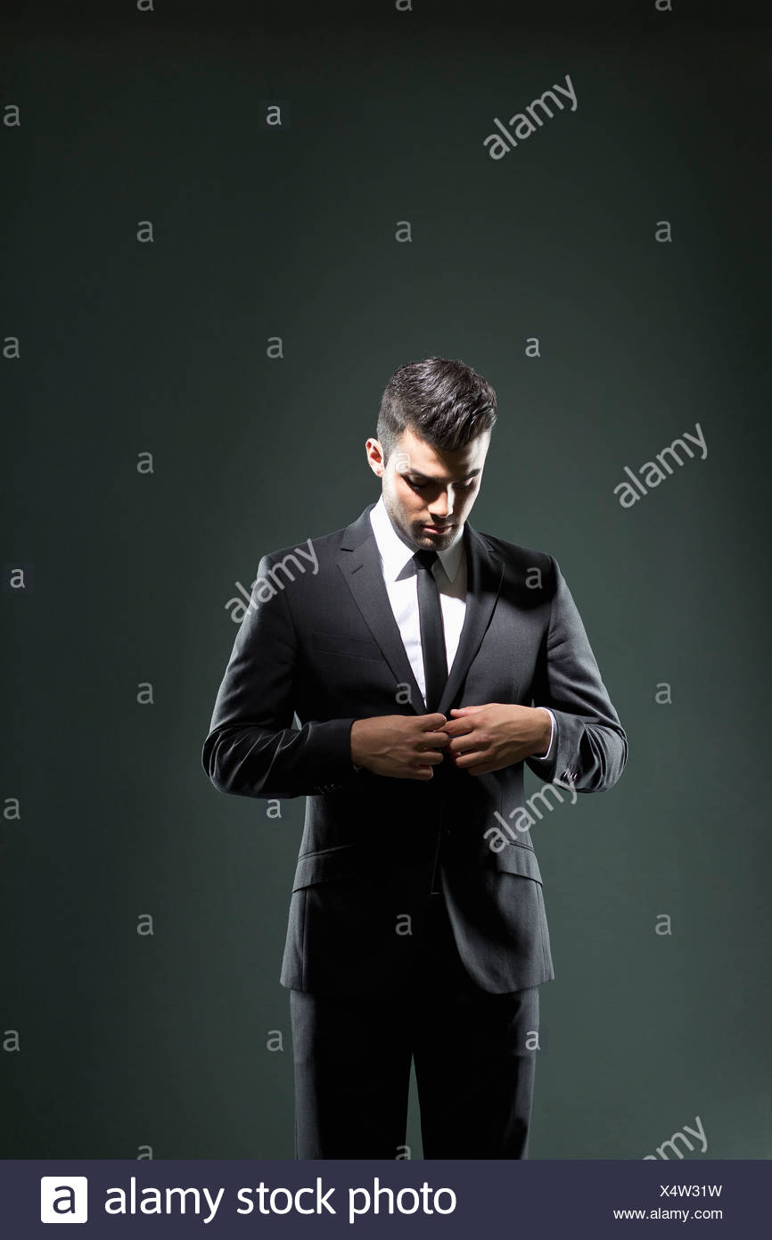 Businessman buttoning suit jacket - Stock Image