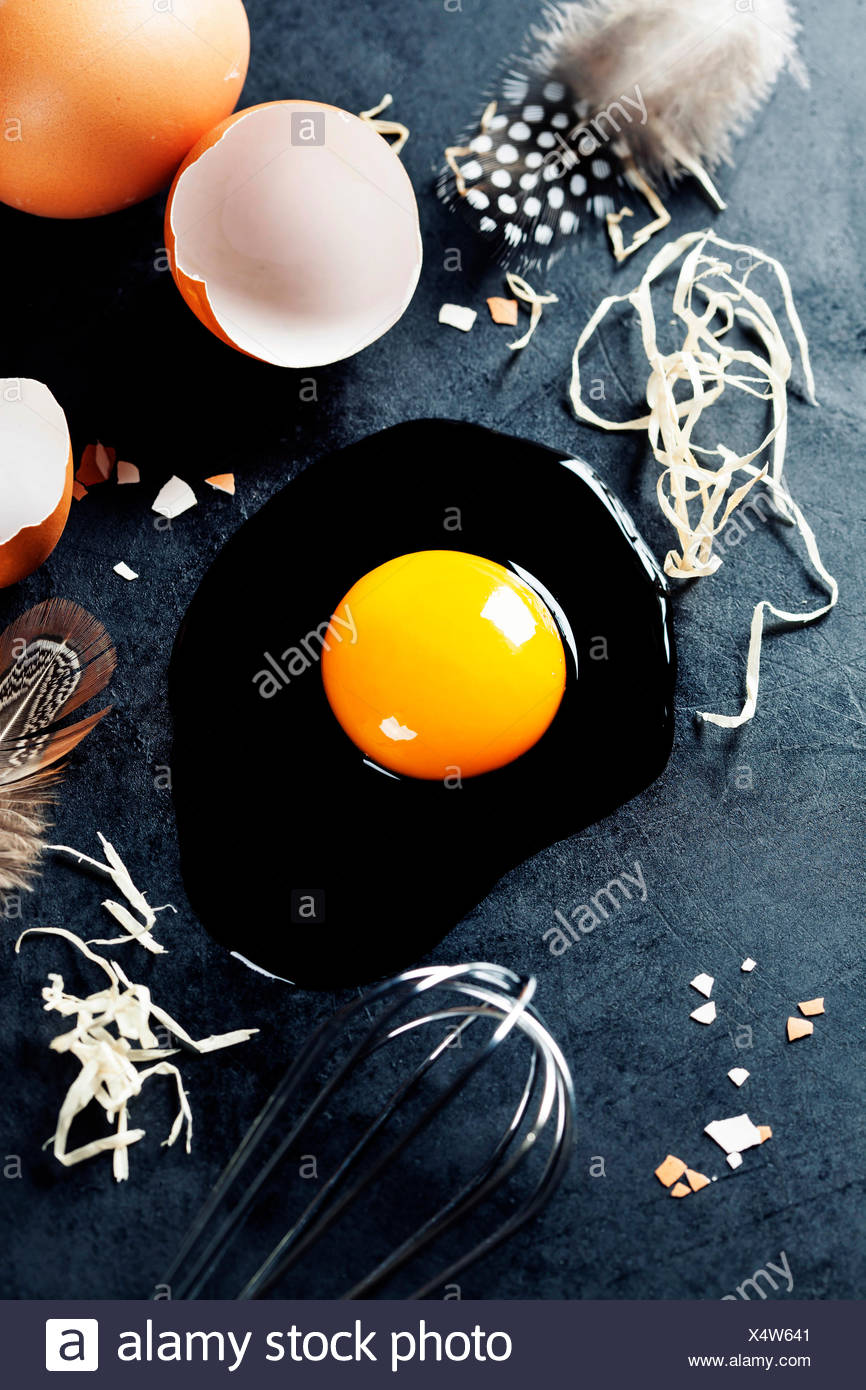 Fresh eggs with straw and  feathers  on a dark background Stock Photo