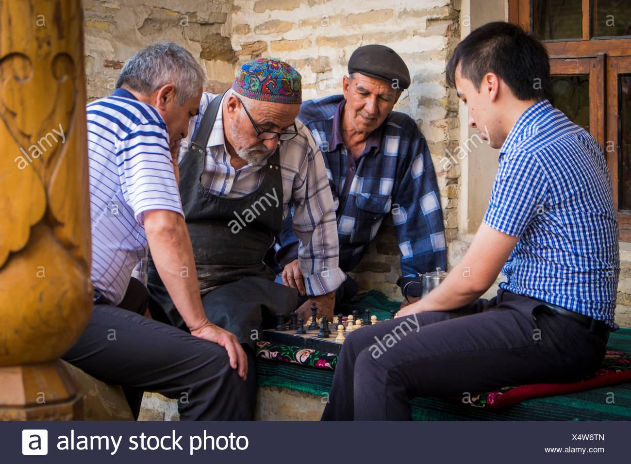 Bukhara, Uzbekistan, Central Asia. Group of mens playing chess. - Stock Image