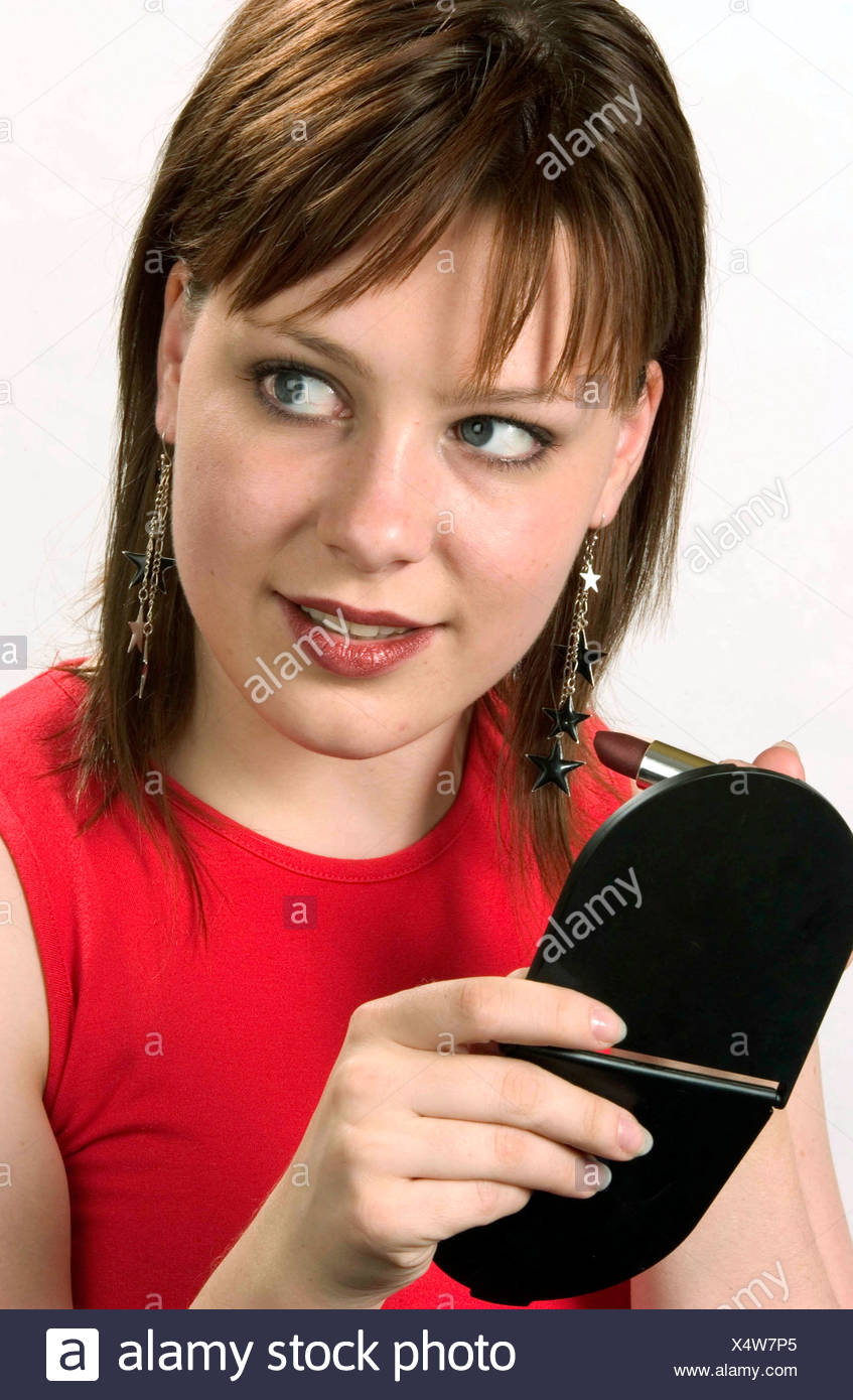 Female shoulder length brunette hair wearing long earrings silver stars and red sleeveless top, holding black compact mirrand - Stock Image