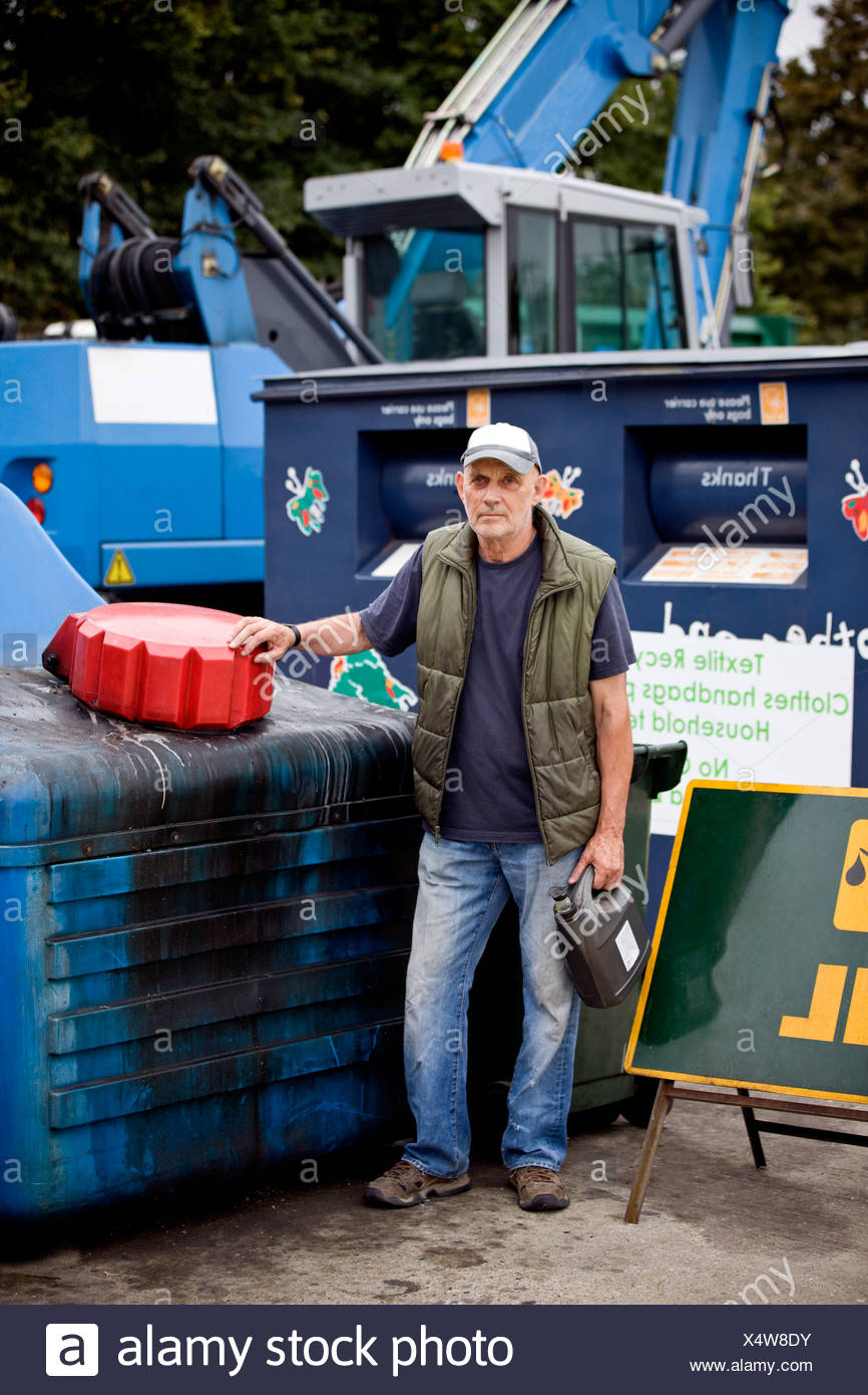 A senior man standing next to a recycling container for oil - Stock Image