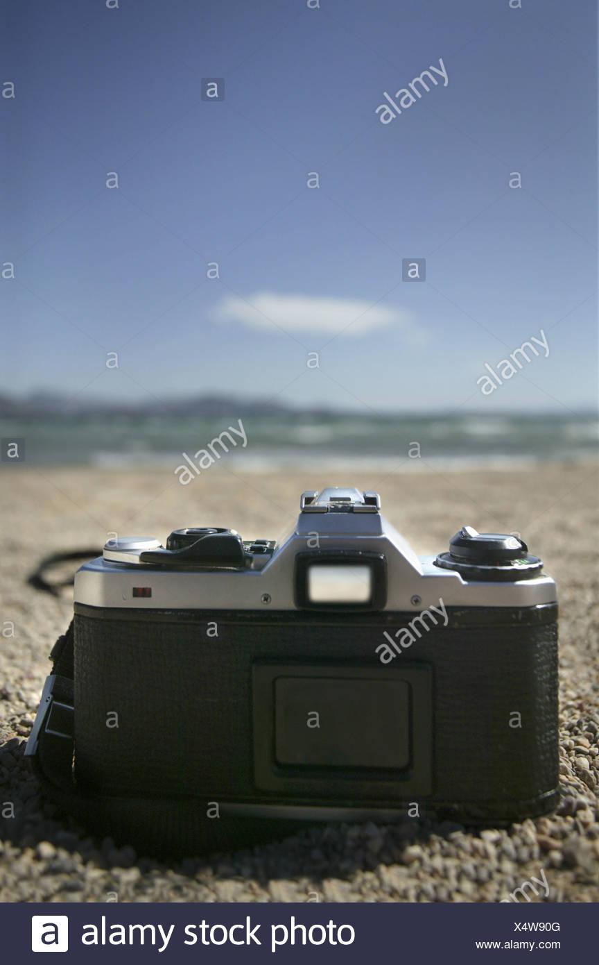 camera lying on the beach - Stock Image