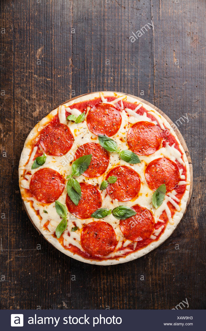 Pepperoni Pizza with basil leaves on wooden table - Stock Image