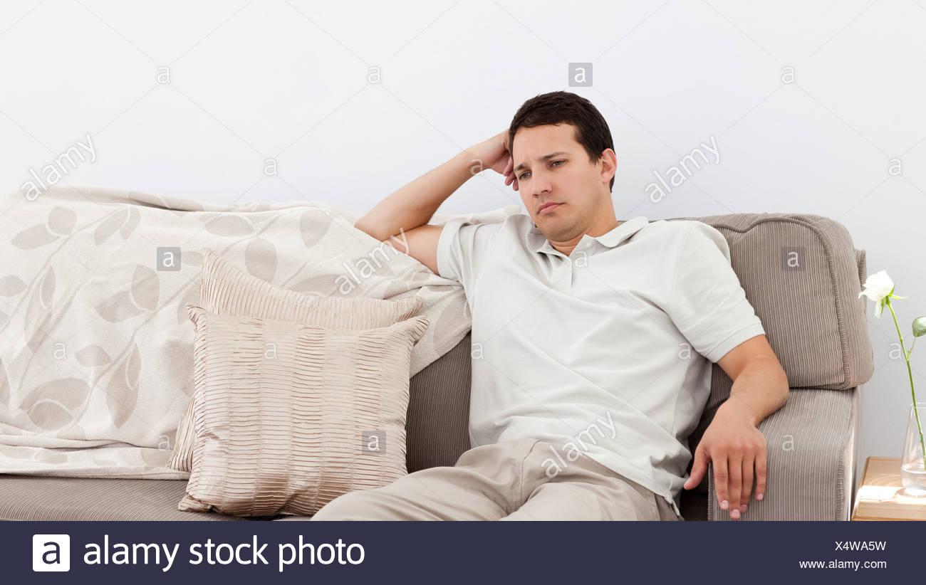 Depressed man thinking on the sofa - Stock Image