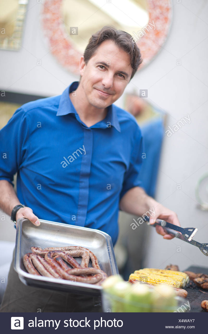 Mature man barbecuing sausages - Stock Image