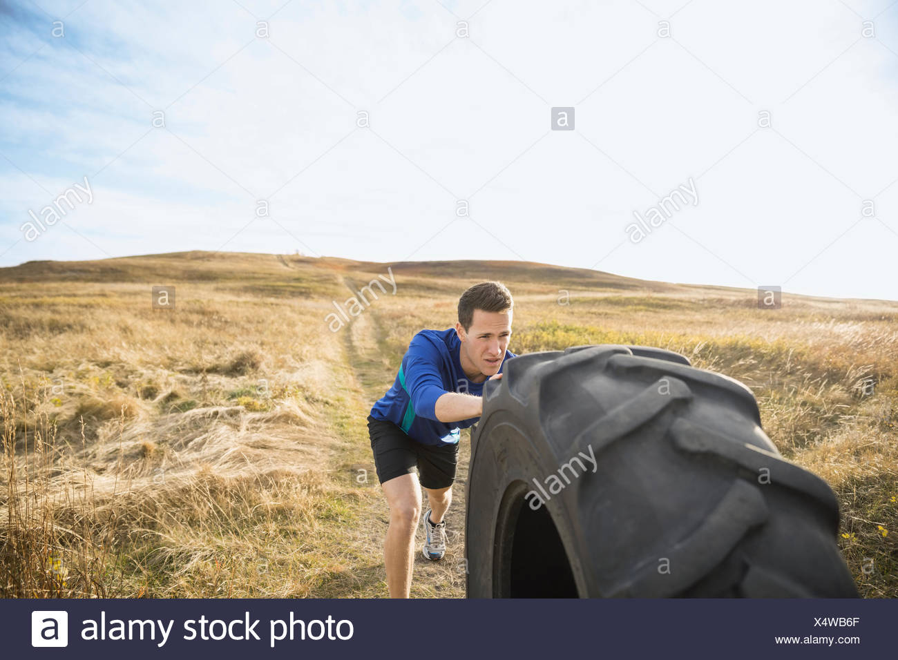 Man pushing crossfit tire in sunny rural field - Stock Image