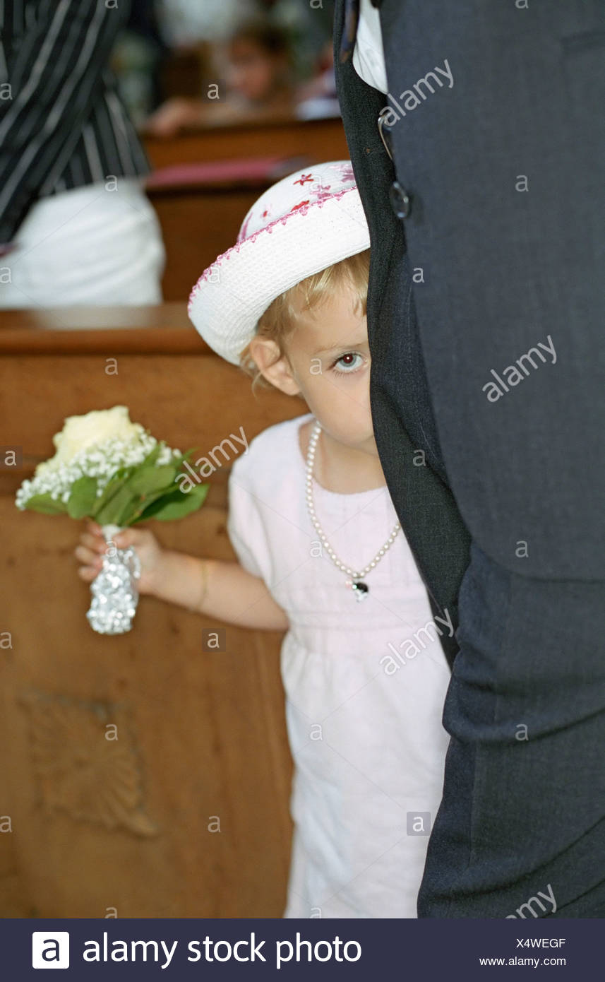 Little Girl in a white Dress with a Bunch of Flowers in her Hand hiding behind a Grown-Up - Stock Image