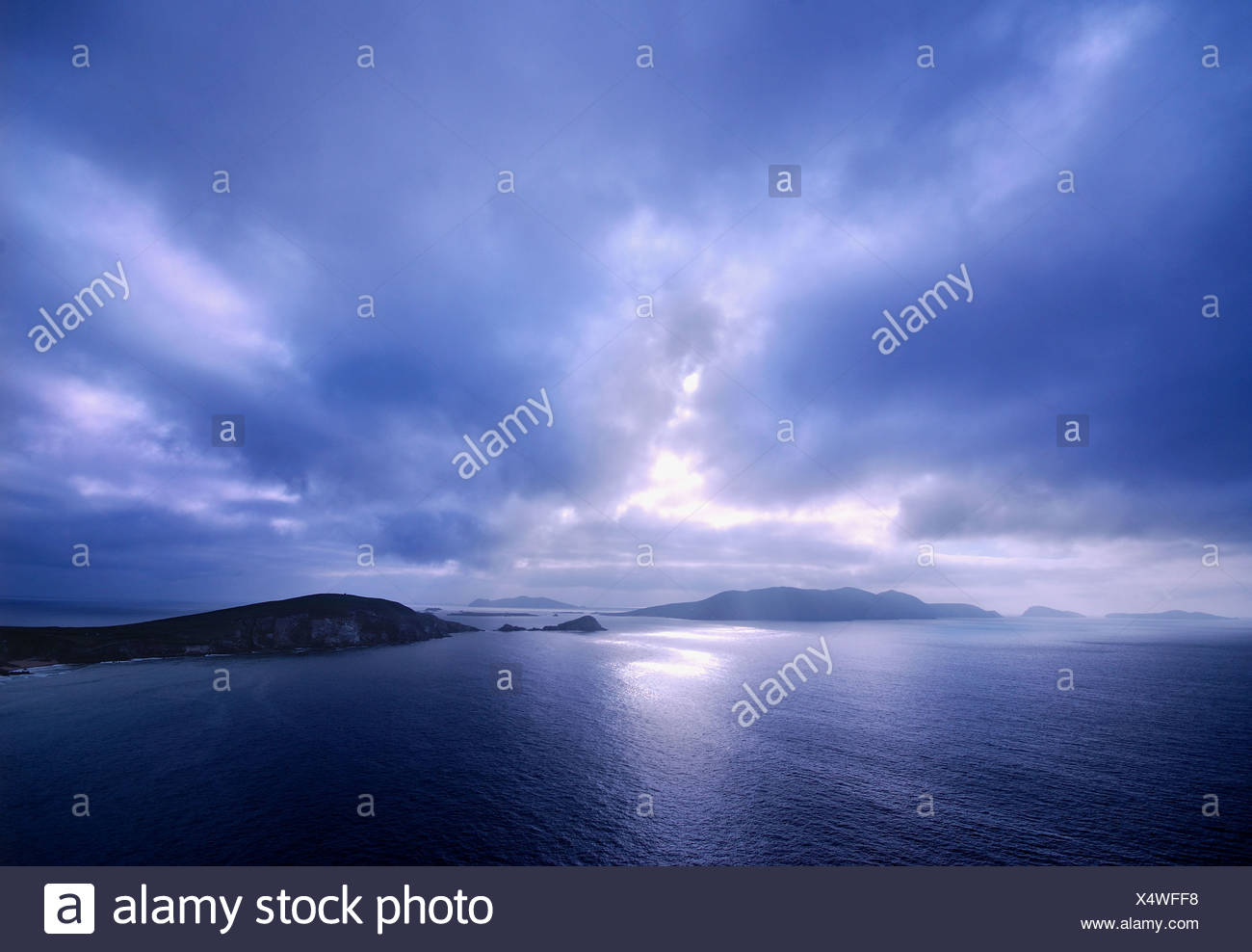the sun setting behind the blasket islands in slea head near dingle in kerry in the west of ireland,the most westerly point in Stock Photo