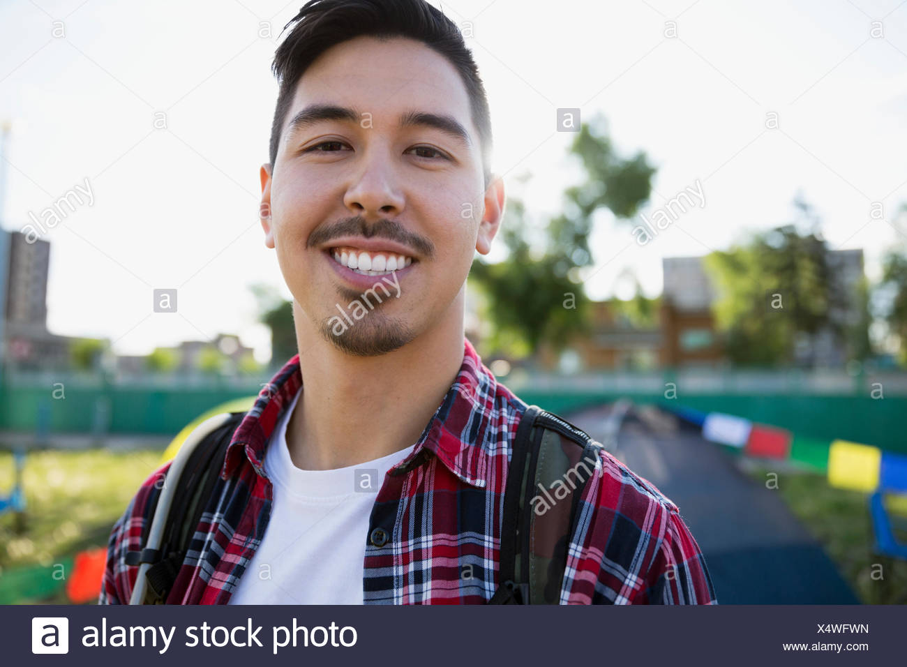 Portrait smiling young man with black hair and stubble smiling at summer music festival campsite - Stock Image