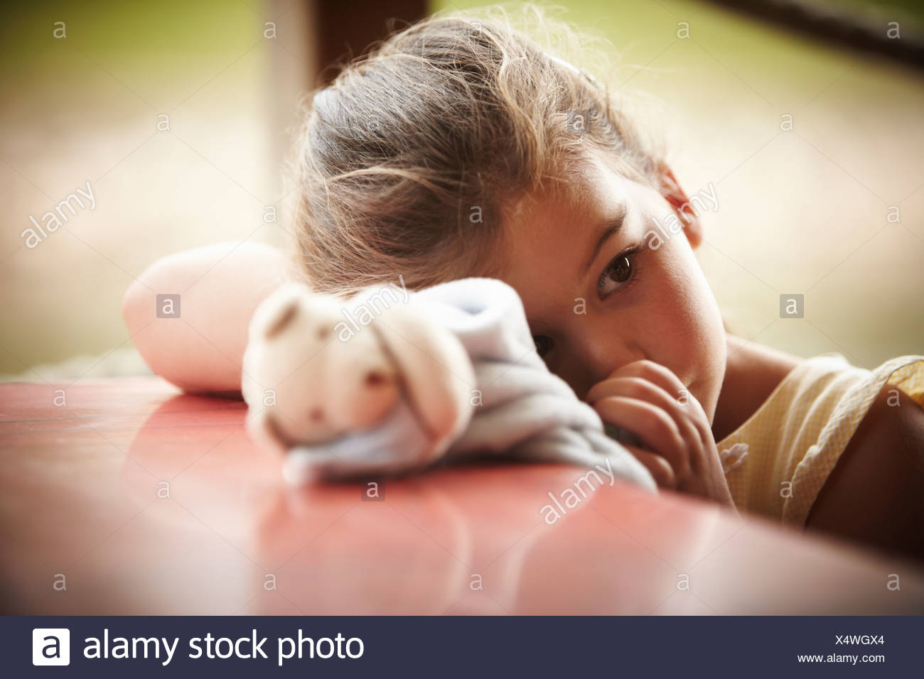 Close up of girl with stuffed animal sucking thumb - Stock Image