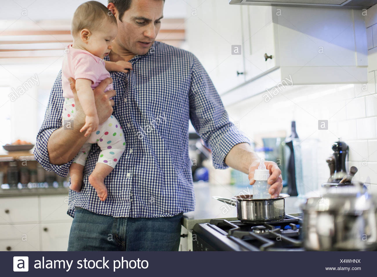 Father heating up baby bottle - Stock Image