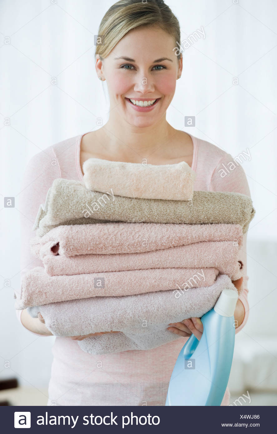 Woman holding folded towels - Stock Image