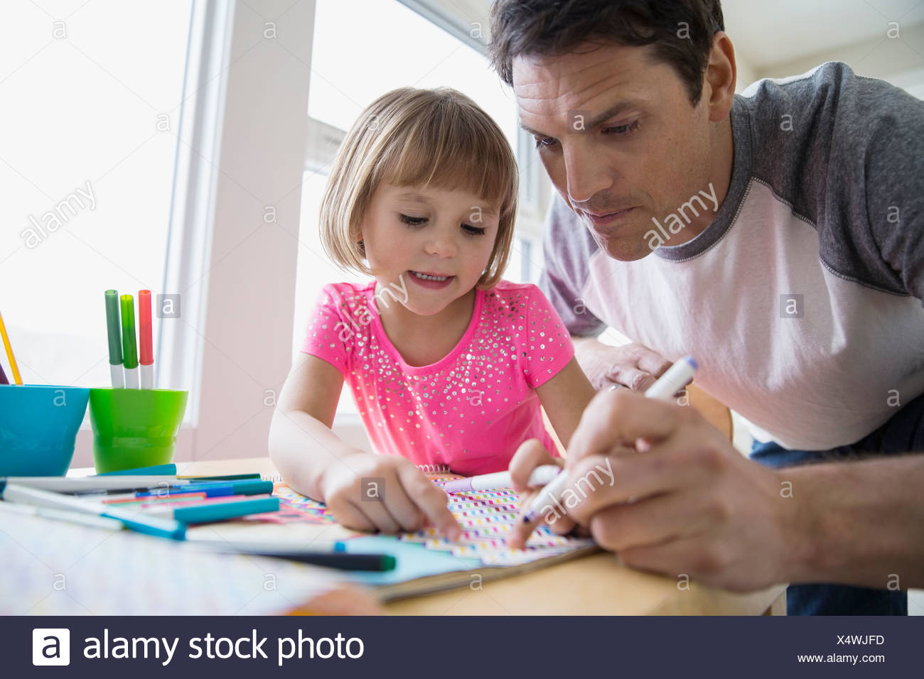 Father and daughter making paper crafts at table - Stock Image