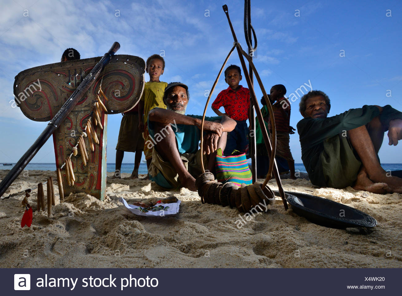 Locals sitting by a canoe sell goods to people who come ashore. - Stock Image