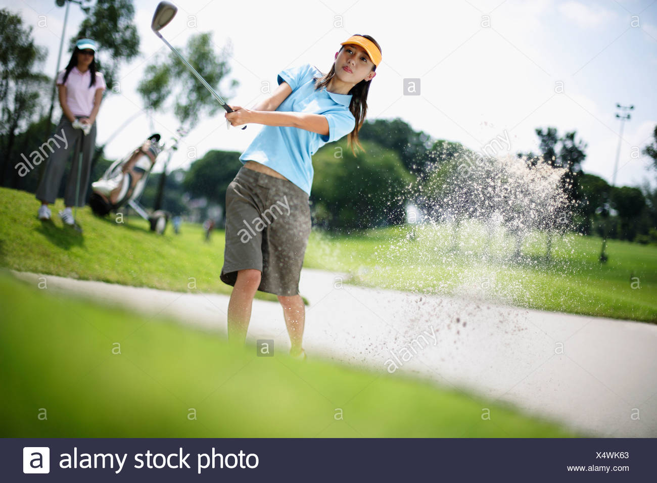 Woman playing golf with woman in background - Stock Image