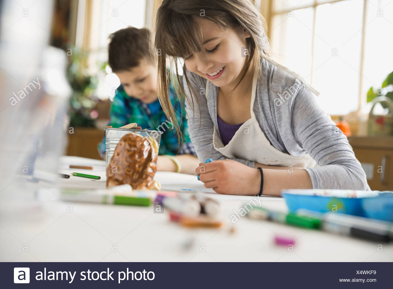 Portrait of girl drawing in art class - Stock Image