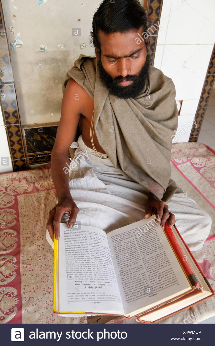 Temple priest reading the Bhagavad Gita. The temple is located on the Goverdan Parikrama pilgrimage trail Goverdan. India. - Stock Image