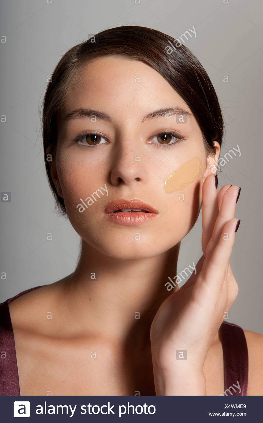 Step By Step Make Up Female Short Brunette Hair Applying Foundation To Her Cheek Fingertips Unsmiling Looking Into Distance Stock Photo Alamy