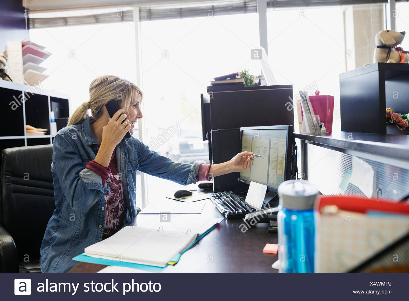 Dog daycare owner scheduling appointment at desk - Stock Image