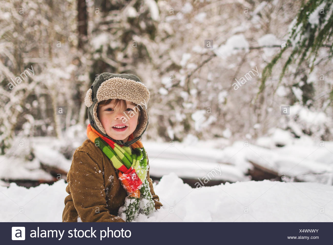 Smiling boy in forest in winter Stock Photo