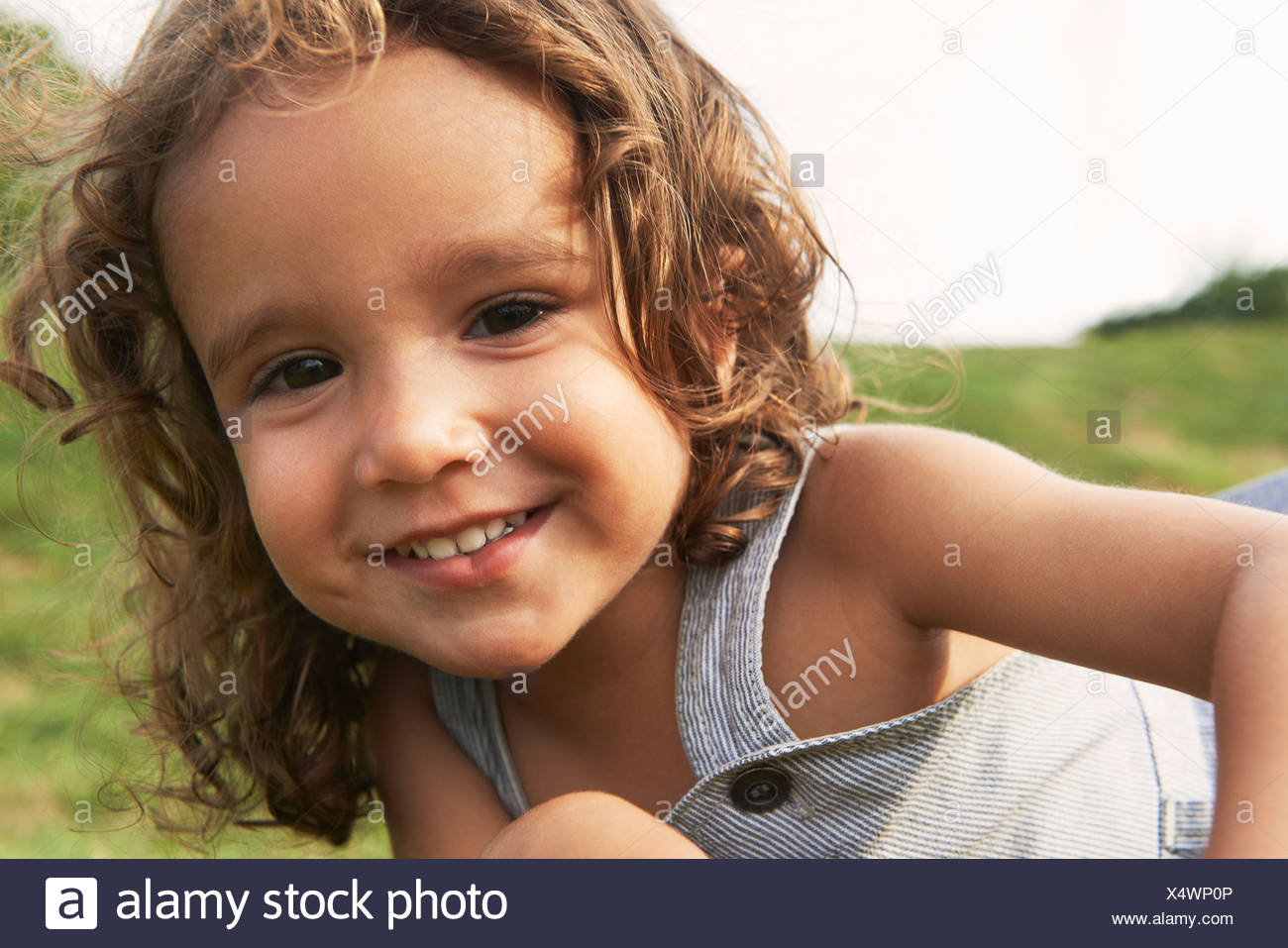 Portrait of young boy with brown hair, smiling - Stock Image
