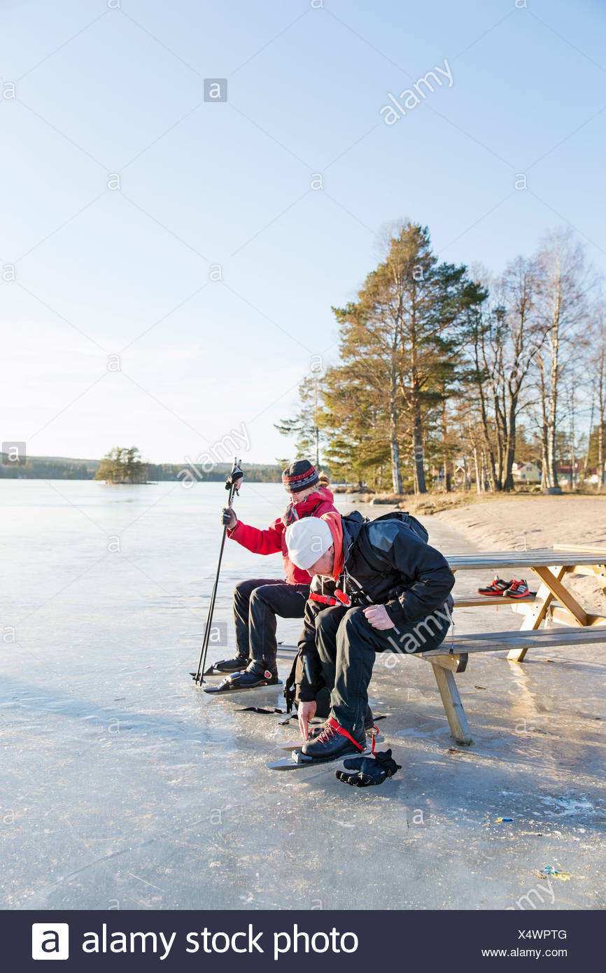 Sweden, Gastrikland, Edsken, Mature woman and man ice skating on frozen lake - Stock Image