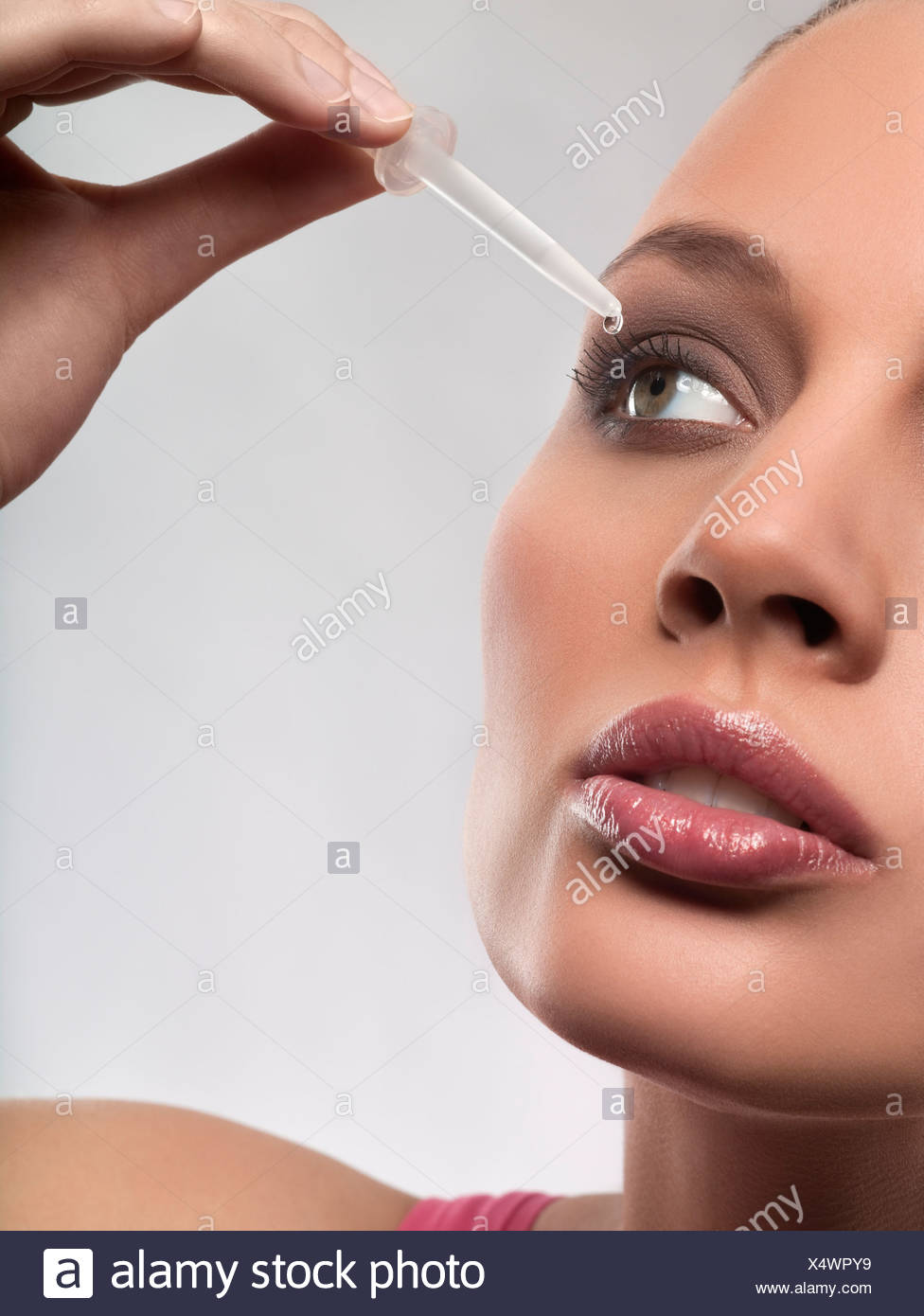 Young woman putting eye drops in eye, studio shot - Stock Image