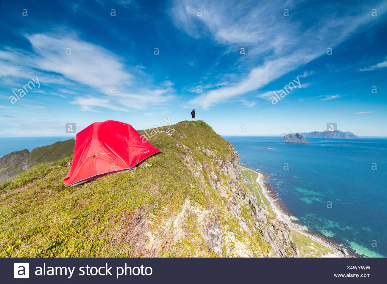 Tent and hiker on mountain ridge overlooking the sea Sorland Vaeroy Island Nordland county Lofoten archipelago Norway Europe - Stock Image