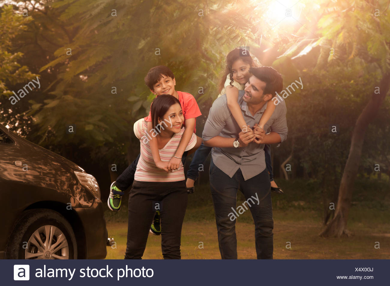 Mother and father carrying children on back in park Stock Photo